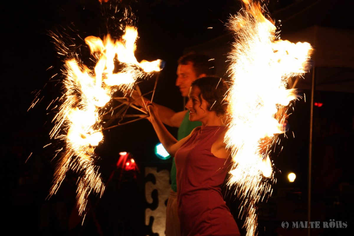 Woman performing with fire fans during the Berlin juggling convention